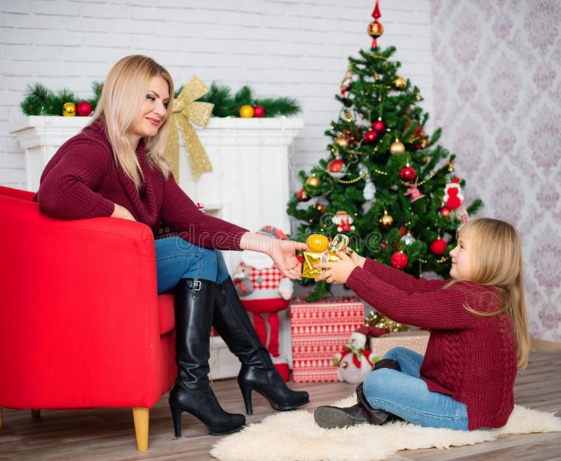Le portrait de la maman de brune et de petit donner de fille se présente pour le MAS de x et les vacances de nouvelle année Famil photo libre de droits