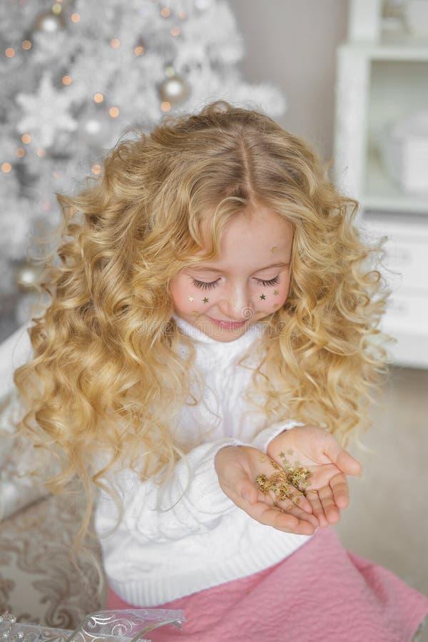 Le portrait de la petite fille assez blonde regarde des confettis des mains dans le studio de Noël photographie stock