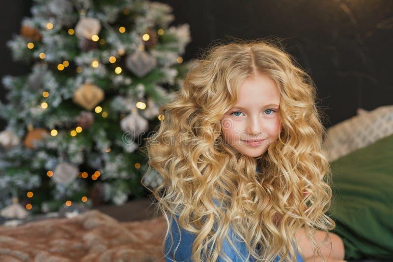 Le portrait de la petite fille assez blonde se repose et sourit sur un lit dans le temps de Noël image stock