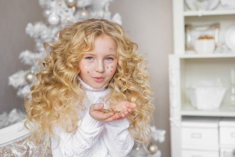 Le portrait de la petite fille assez blonde souffle à des confettis aux mains dans le studio de Noël image stock