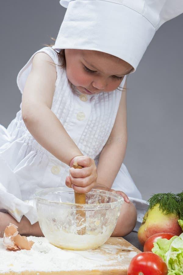 Le portrait de la petite fille caucasienne concentrée par bien dans le cuisinier Uniform Working With battent photos stock