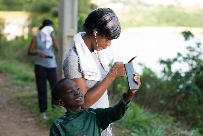 Le portrait de mère et de fils utilise le téléphone portable dehors images libres de droits