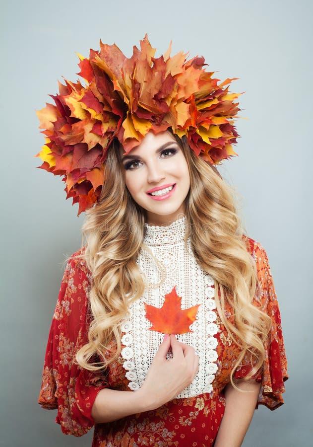 Le portrait de mode de beaut? de la jolie femme d'automne dans l'automne lumineux laisse la couronne avec la feuille d'?rable rou photographie stock libre de droits