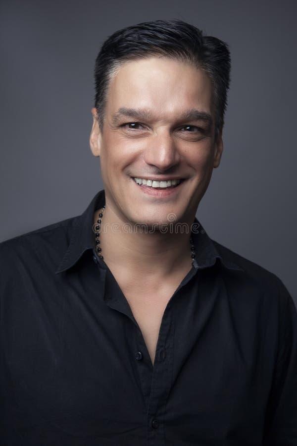 Le portrait de mode du jeune homme dans la chemise noire pose au-dessus du mur avec des ombres de contraste image stock