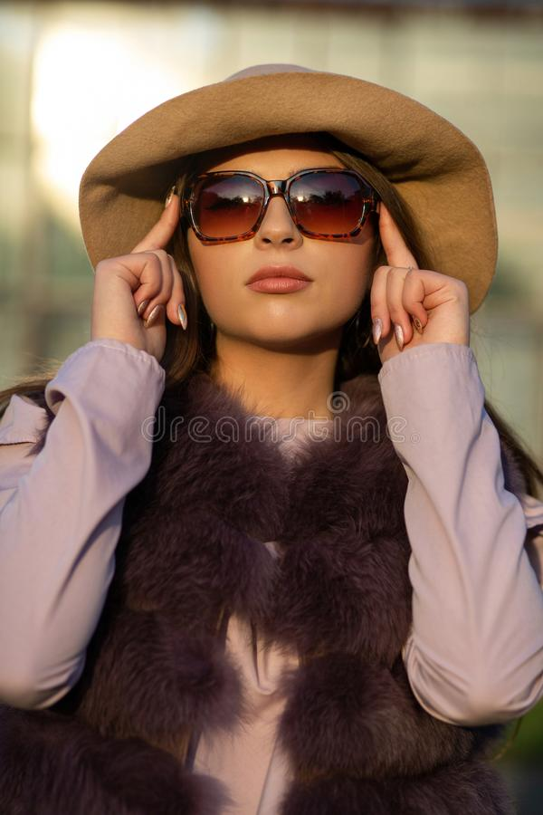 Le portrait de mode du modèle élégant de brune porte le chapeau, les verres et le manteau photo libre de droits
