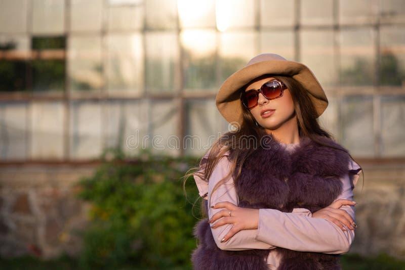 Le portrait de mode du modèle de brune porte le chapeau, les verres et le manteau L'espace vide images libres de droits