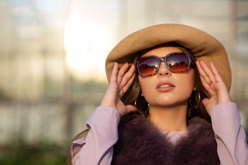Le portrait de mode de rue du modèle élégant de brune porte le chapeau, les verres et le manteau L'espace vide photos libres de droits