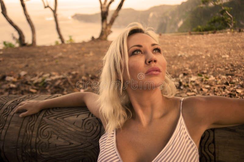 Le portrait de mode de vie d'extérieur de la jeune belle et décontractée femme blonde se penchant sur le tronc d'arbre appréciant image libre de droits
