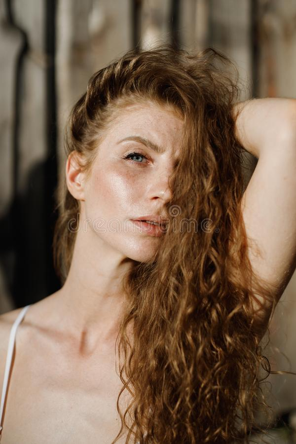 Le portrait de photo d'une belle fille avec de longs cheveux rouges bouclés à la lumière du soleil dans la perspective d'un mur e photo stock