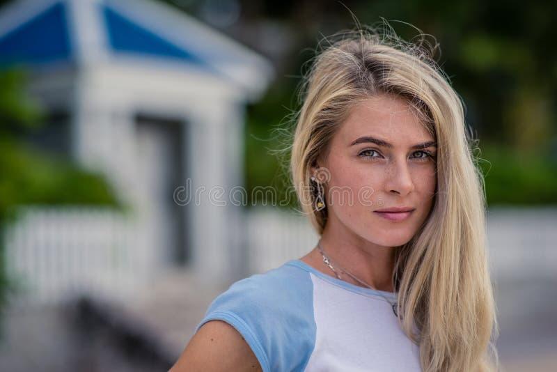 Le portrait de plan rapproché d'été de la belle fille blonde avec de longs cheveux et beaux yeux pose contre une barrière blanche photographie stock libre de droits