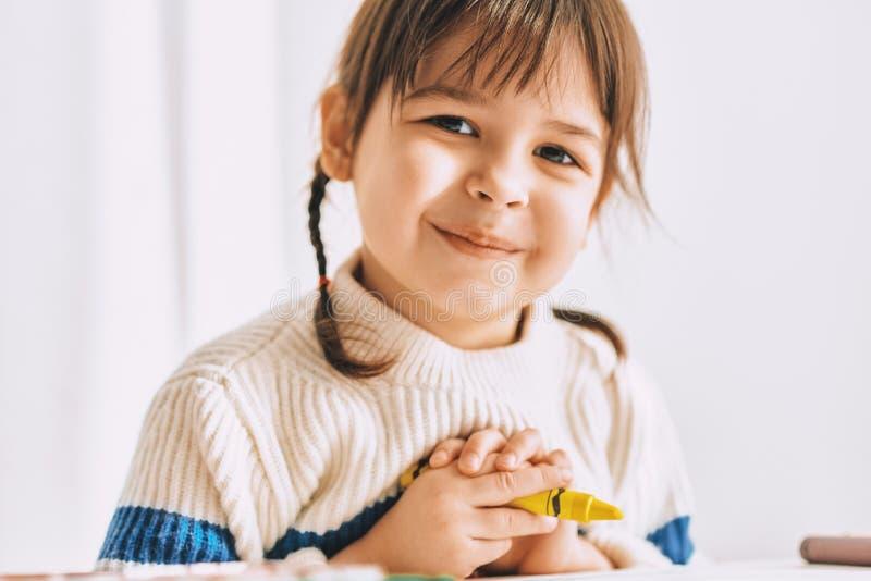 Le portrait de plan rapproché de la belle petite fille heureuse peint avec des crayons d'huile, se reposant au bureau blanc à la  photos libres de droits
