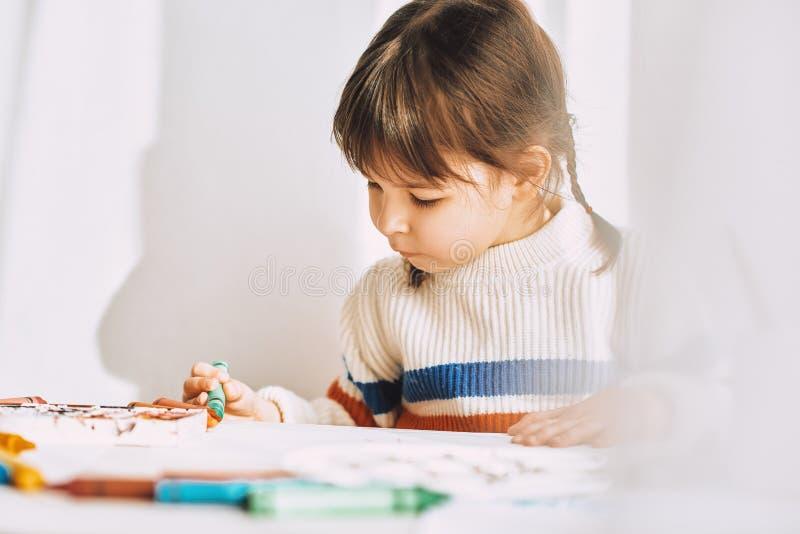 Le portrait de plan rapproché de la belle petite fille peint avec des crayons d'huile, se reposant au bureau blanc à la maison photographie stock