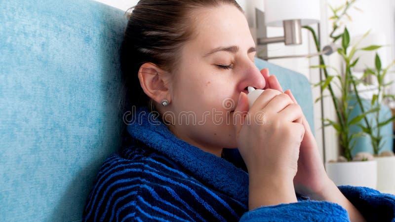 Le portrait de plan rapproché de la femme malade a attrapé la pulvérisation nasale d'utilisation à froid pour arrêter la rhinite photos libres de droits