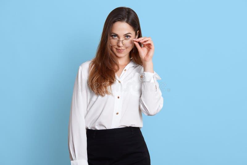 Le portrait de plan rapproché de la femme tient des verres avec la main et les regards à la caméra La dame d'affaires porte la ch images libres de droits