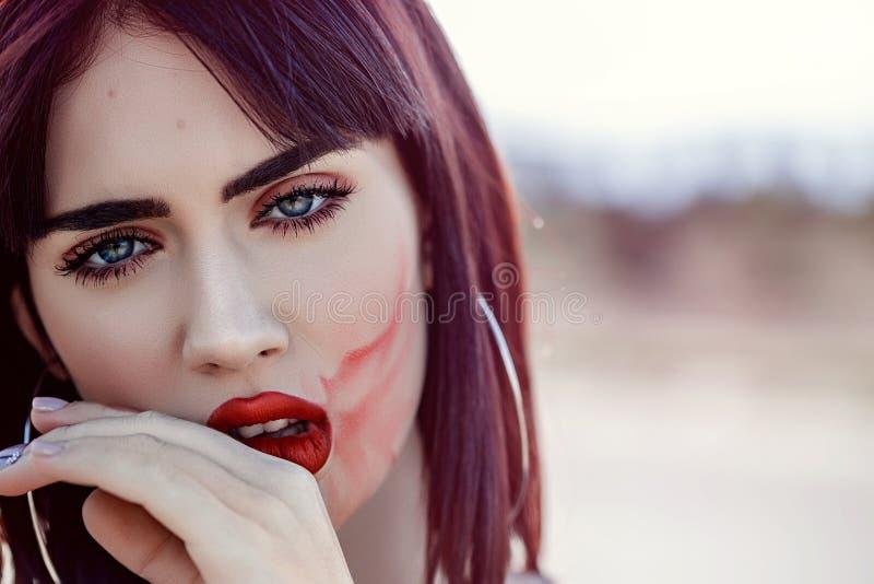 Le portrait de plan rapproch? de la belle jeune femme avec la peau fra?che propre a touch? son rouge ? l?vres de visage et de cal photo stock