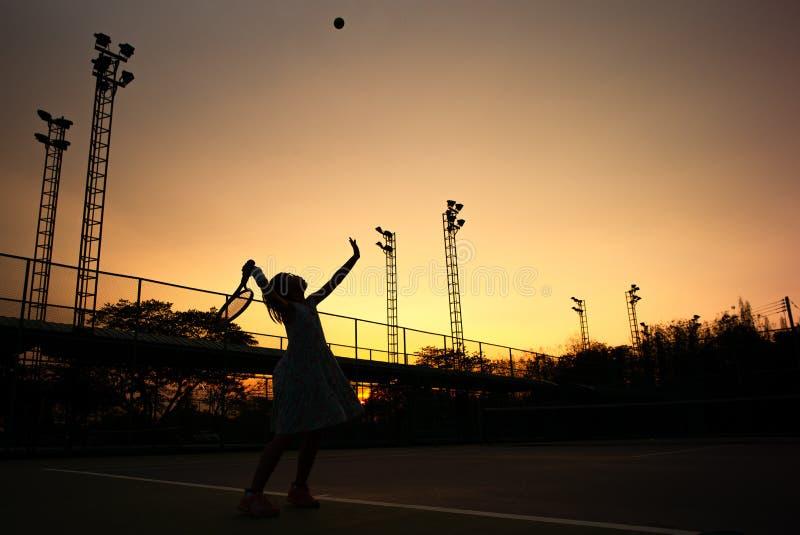 Le portrait de silhouette de la fille asiatique joue au tennis à la cour extérieure avec le ciel de coucher du soleil à l'arri photographie stock libre de droits