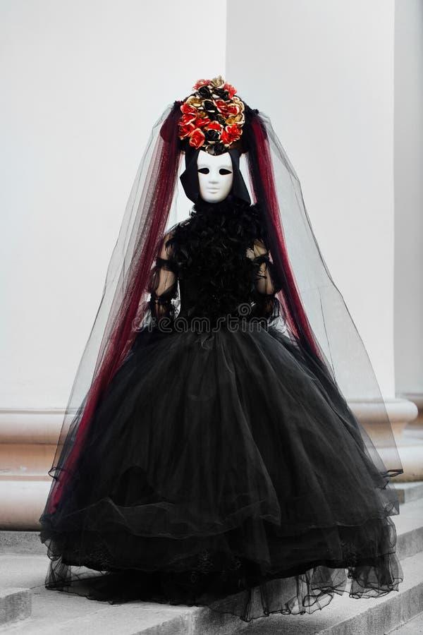 Le portrait de sorcière dans la robe noire de vintage, le masque blanc couvre le visage Veuve Halloween de femme images libres de droits