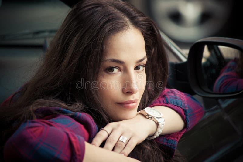 Le portrait de sourire de jeune femme se reposent dans la voiture se penchant sur la fenêtre photos stock