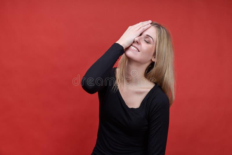 Le portrait de studio d'une jeune femme aux cheveux longs s'est habillé dans le bl noir image stock