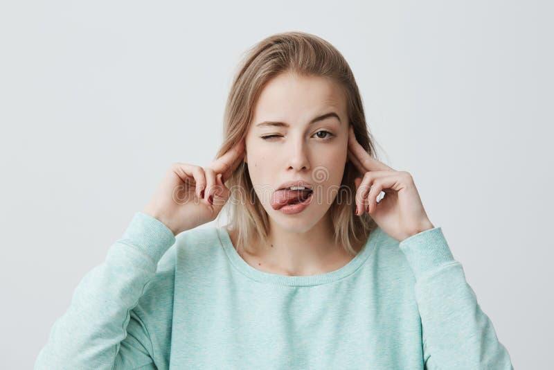 Le portrait de studio jeunes des oreilles de froncement de sourcils et de branchement femelles blondes ennuyées et contrariées av photo stock