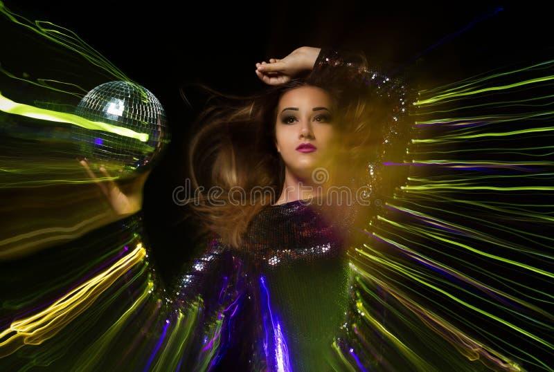 Le portrait de studio de la belle femme tient la boule de disco avec les rayons colorés photo libre de droits