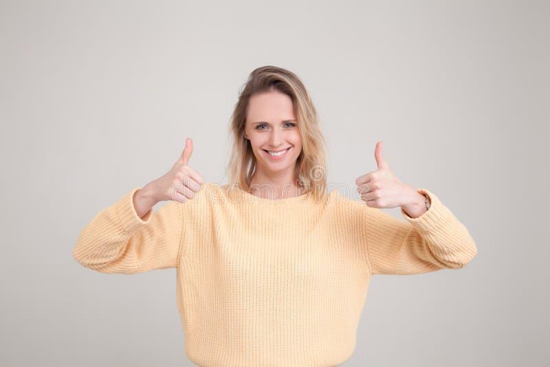 Le portrait de taille- disparaissent jeune femme blonde souriant et faisant des pouces vers le haut de signe repr?sentation du re photo stock