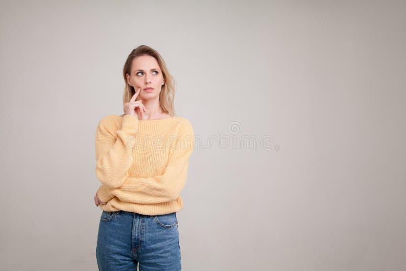 Le portrait de taille- de la femme blonde avec l'expression perplexe de visage, garde son doigt sur la joue, regarde de c?t? chan photo stock