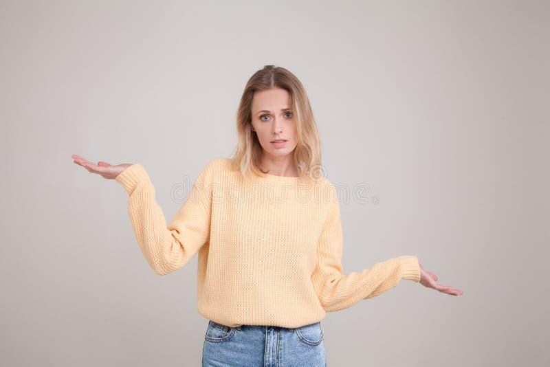 Le portrait de taille- de la jeune femme blonde avec ?motion confuse, gesticule des ?paules car elle ne conna?t pas la r?ponse, ? photographie stock libre de droits
