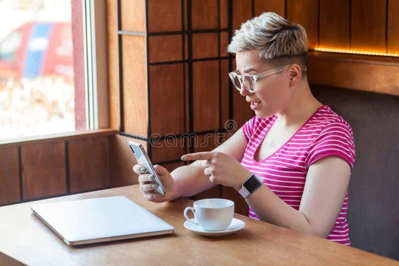 Le portrait de vue de côté du jeune blogger enthousiaste avec les cheveux courts dans le T-shirt rose se repose en café, tient le photo libre de droits