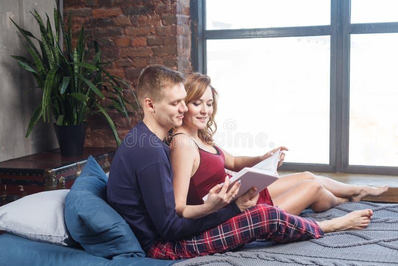 Le portrait de vue de côté de la belle jeune famille heureuse ont un repos dans la chambre à coucher, dans l'album de participati images libres de droits