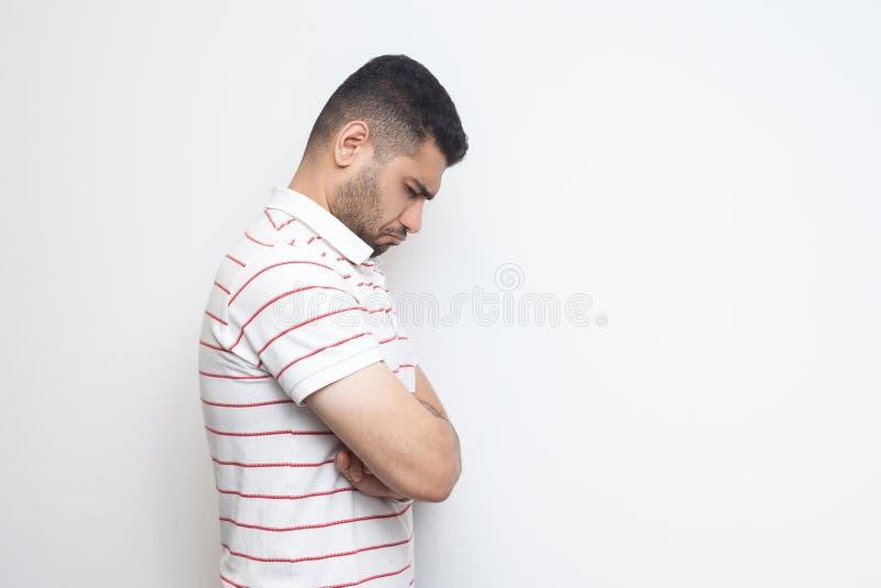 Le portrait de vue de côté de profil d'o triste seul a enfoncé le jeune homme barbu dans la position rayée de T-shirt, maintenant photographie stock