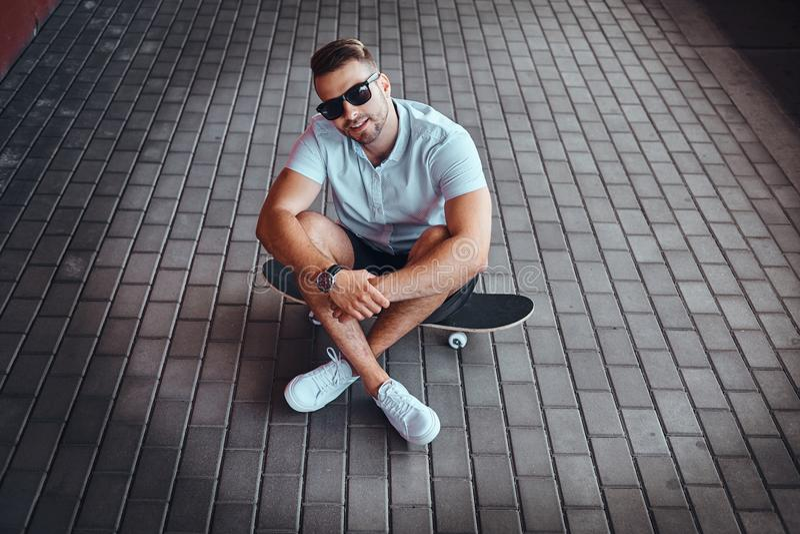 Le portrait de vue supérieure d'un type à la mode beau de patineur dans des lunettes de soleil s'est habillé dans une chemise bla photo stock