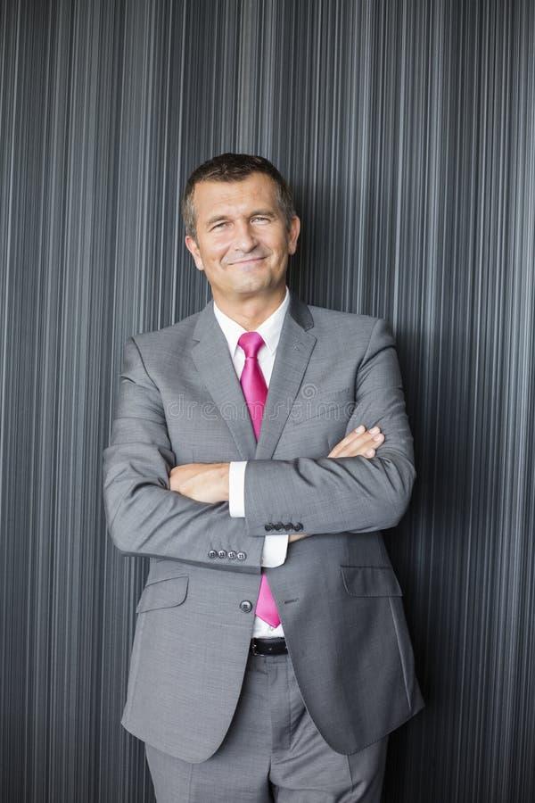 Le portrait des bras debout de sourire d'homme d'affaires mûr a croisé contre le mur photos libres de droits