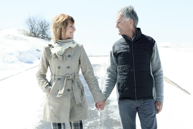 Le portrait des couples supérieurs heureux en hiver assaisonnent images stock