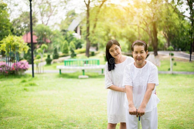 Le portrait des femmes asiatiques pluses ?g? se tenant et marchant pour faire physique avec le b?ton ext?rieur, gardien salut et  photographie stock