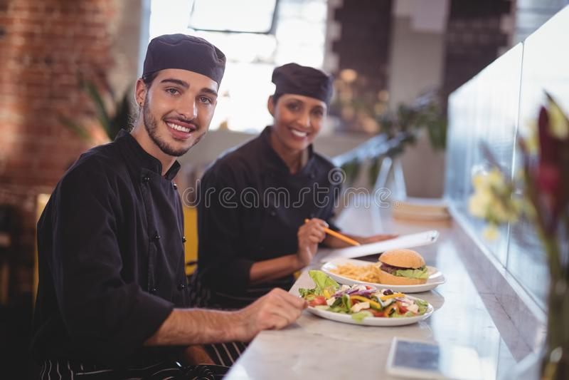 Le portrait des jeunes de sourire attendent le personnel s'asseyant avec la nourriture et le presse-papiers au compteur images libres de droits