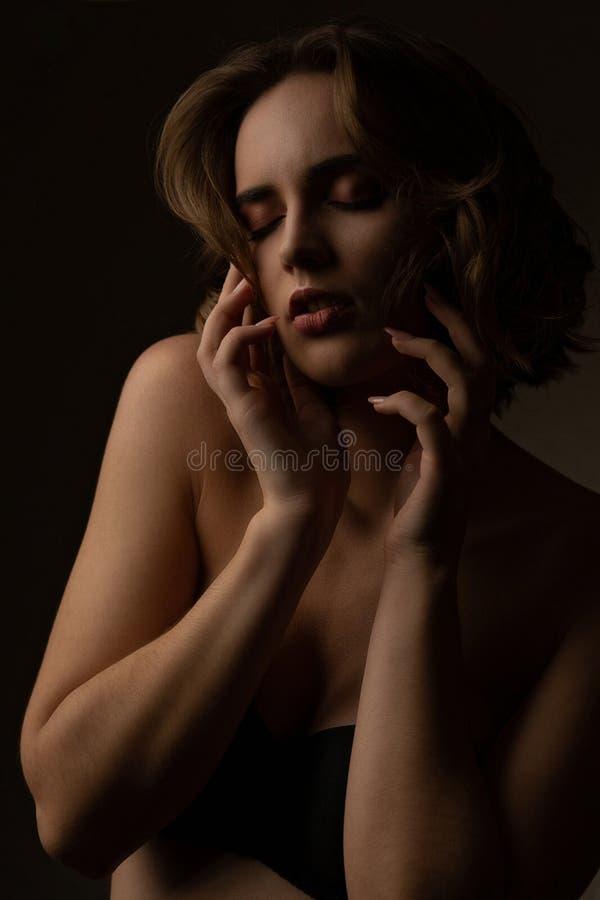 Le portrait dramatique du modèle tendre de brune avec les cheveux onduleux porte le soutien-gorge, posant dans les ombres photo stock