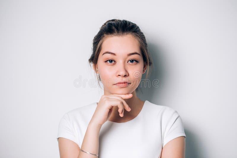 Le portrait du beau bleu a observé la fille sur un fond blanc photo libre de droits