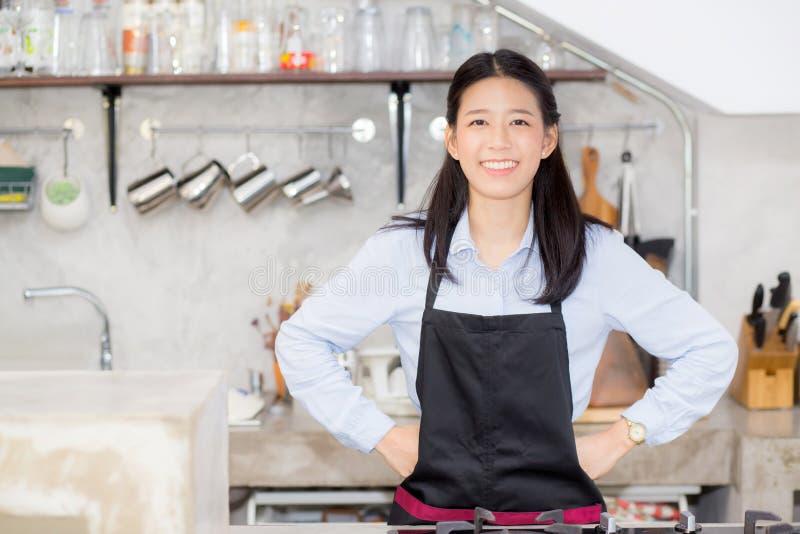 Le portrait du beau jeune barman, femme asiatique est un employé se tenant dans le contre- café photographie stock libre de droits