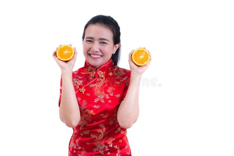 Le portrait du beau jeune Chinois asiatique d'usage de femme habillent le cheongsam ou le qipao traditionnel tenir l'orange juteu image libre de droits