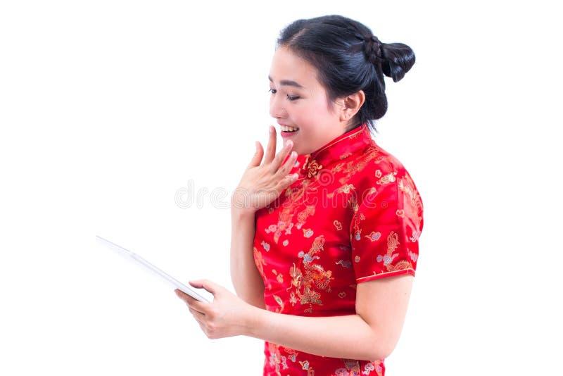 Le portrait du beau jeune Chinois asiatique d'usage de femme habillent le cheongsam ou le qipao traditionnel utilisant le comprim images stock