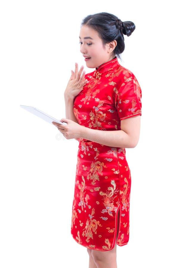 Le portrait du beau jeune Chinois asiatique d'usage de femme habillent le cheongsam ou le qipao traditionnel utilisant le comprim image stock