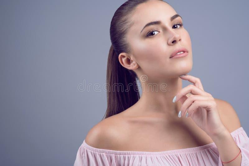 Le portrait du beau jeune modèle aux cheveux foncés avec la peau parfaite et la nudité humide composent sur le fond gris photo stock