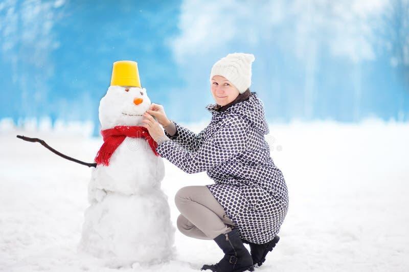 Le portrait du beau Moyen Âge de sourire/mûrissent/bonhommes de neige femelles plus anciens de bâtiment en parc neigeux photo libre de droits