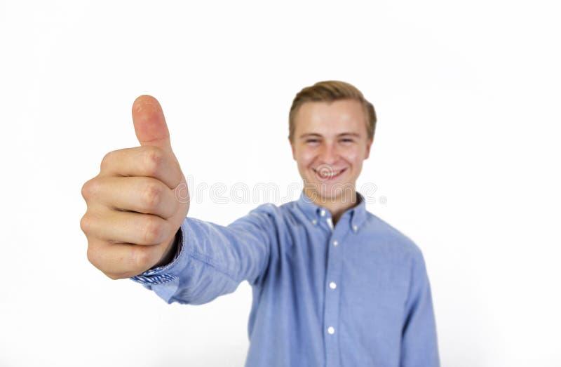 Le portrait du garçon frais avec la chemise bleue montrant des pouces lèvent le signe image stock