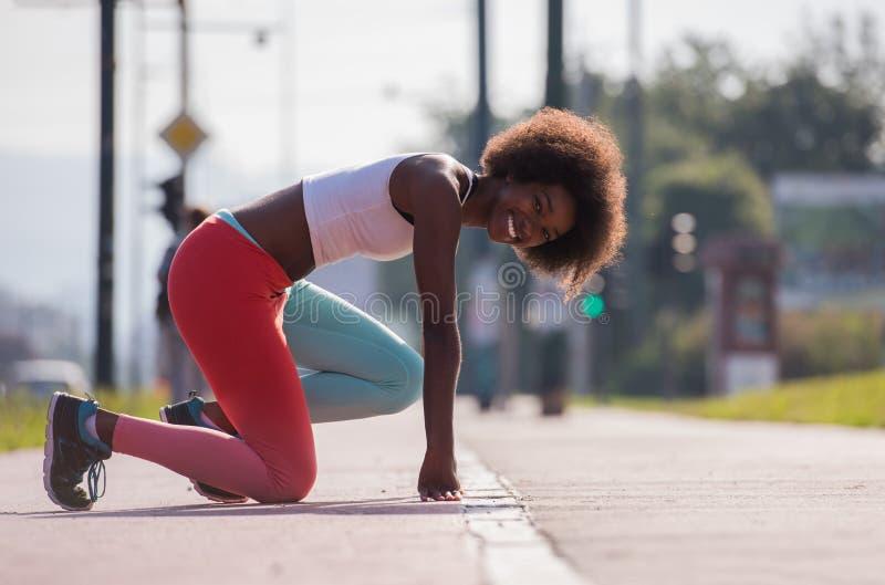 Le portrait du jeune étirage sportif de femme d'afro-américain se surpassent images stock
