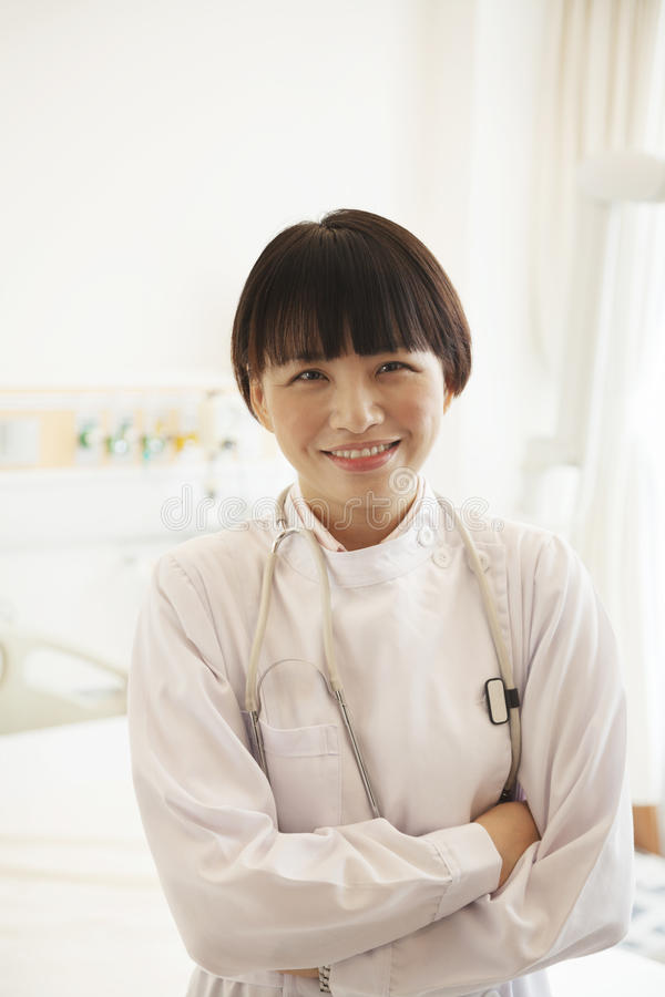 Le portrait du jeune docteur féminin de sourire avec des bras a croisé dans un hôpital images stock