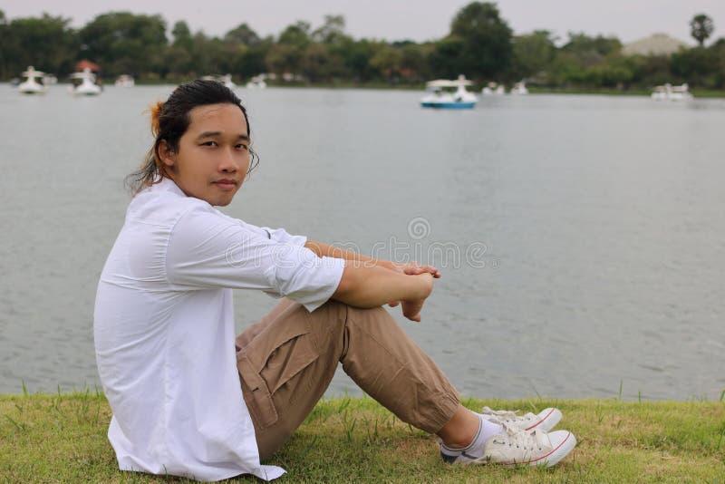 Le portrait du jeune homme asiatique s'asseyant sur une herbe verte en rivière de nature détendent le temps images stock
