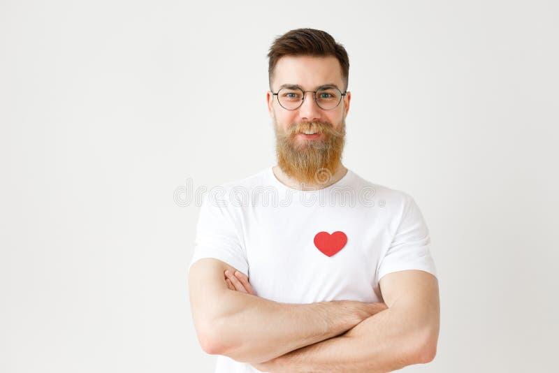 Le portrait du jeune homme barbu beau porte autour des lunettes et le T-shirt occasionnel blanc avec le coeur rouge, garde des ma image libre de droits
