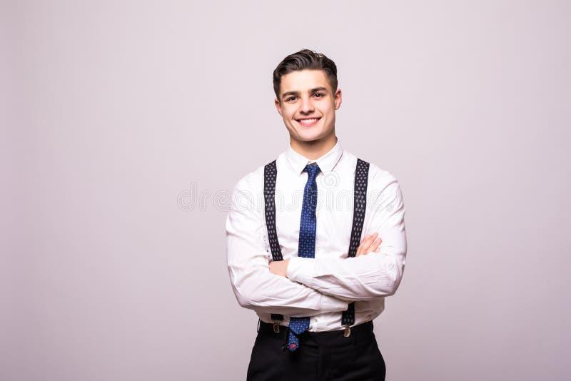 Le portrait du jeune homme de sourire heureux utilisant une chemise blanche se tenant avec des mains s'est plié contre d'isolemen photographie stock